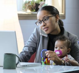 Mother holding baby and working at her computer